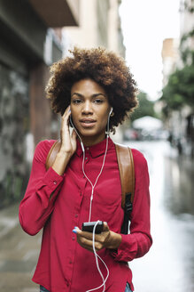 Portrait of young woman hearing music with earphones - EBSF000374