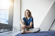 Portrait of smiling mature woman sitting on the floor at her apartment - RBF002032