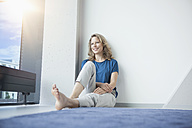 Portrait of smiling mature woman sitting on the floor in her apartment - RBF002035