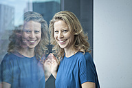 Portrait of smiling mature woman looking through window - RBF002038