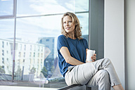 Smiling mature woman looking through window at her apartment - RBF002044