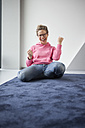 Excited mature woman sitting on the floor of her apartment - RBF002053