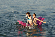 Italy, girl and teenage boy sitting together on airbed splashing with water - LBF000990
