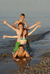 Italy, four children in a row at seafront - LBF000991