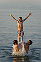 Italy, three teenage boys having fun at seaside - LBF000992