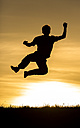 Silhouette of jumping man at sunset - STSF000606
