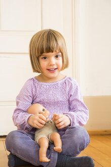 Portrait of smiling little girl playing with doll - LVF002305