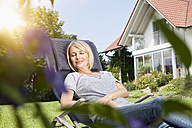 Relaxed woman in deck chair in garden - RBF001912