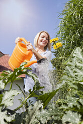 Woman watering plants in garden - RBF001924