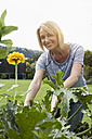 Smiling woman working in garden - RBF001927