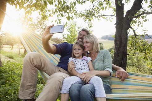 Happy family taking selfie in hammock - RBF001970
