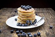 Dish with pile of pancakes, blueberries, sprinkled with icing sugar - LVF002308
