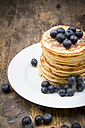Dish with pile of pancakes, blueberries, sprinkled with icing sugar - LVF002311