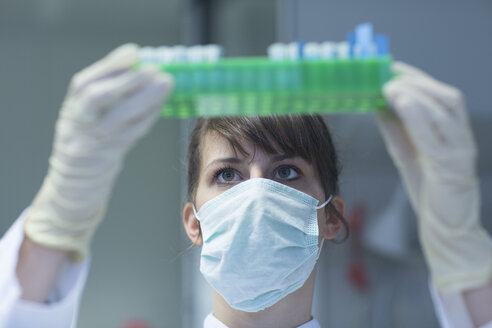 Young female natural scientist with mask and protective gloves working at  labroratory - SGF001110