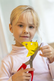 Little girl tinkering with scissors and paper - JFEF000555