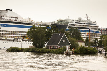Netherlands, Amsterdam, Cruise ship Aida and small house in the foreground - FC000498