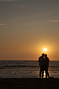 Netherlands, Bloemendaal, lovers on beach at sunset - FC000514