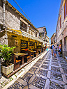 Italy, Sicily, Erice, view to alley with pavement restaurant and gift shop - AMF003275