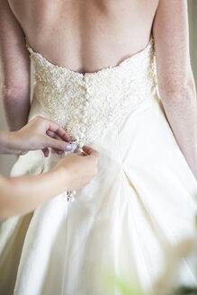Bridesmaid buttoning up bride's wedding dress - ZEF002533