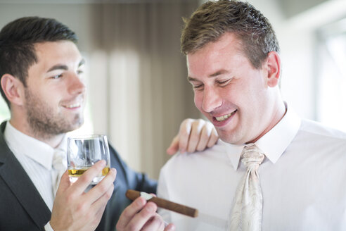 Groom smoking a cigar with best man before wedding - ZEF002540