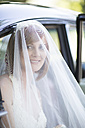 Smiling bride getting out of car before her wedding - ZEF002563