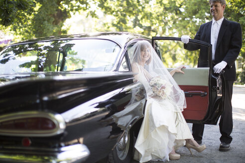 Bride getting out of car before her wedding with driver - ZEF002789