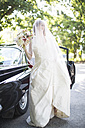 Happy bride outside car - ZEF002569