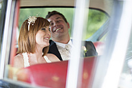 Happy bride and groom in car - ZEF002575