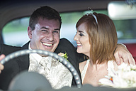 Happy bride and groom in car - ZEF002578