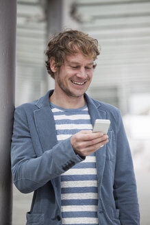Portrait of smiling man with smartphone reading SMS - RBF002085