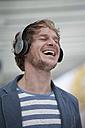 Portrait of happy man with headphones hearing music - RBF002087