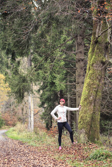 Female jogger leaning on tree trunk in the wood - VTF000352