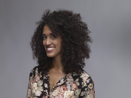 Portrait of smiling young woman with nose ring and Afro in front of grey background - RH000399
