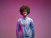 Portrait of smiling young man with Afro in front of pink background - RH000428