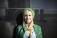 Portrait of smiling woman wearing green cap and leather jacket - RHF000441