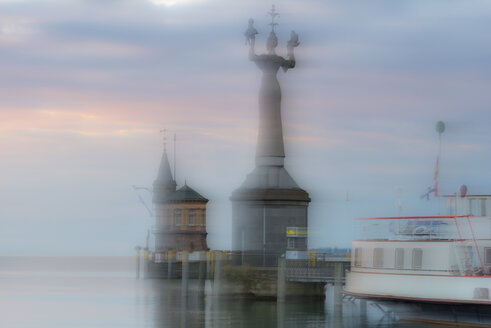 Germany, Baden-Wuerttemberg, Lake Constance, Constance, double exposure of Imperia statue at harbor at dawn - SHF001683