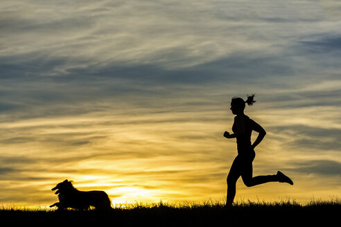 Germany, Female jogger with dog at sunset - STSF000618