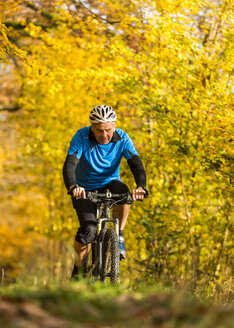 Germany, Baden-Wuerttemberg, Senior man mountain biking in autumn - STSF000628