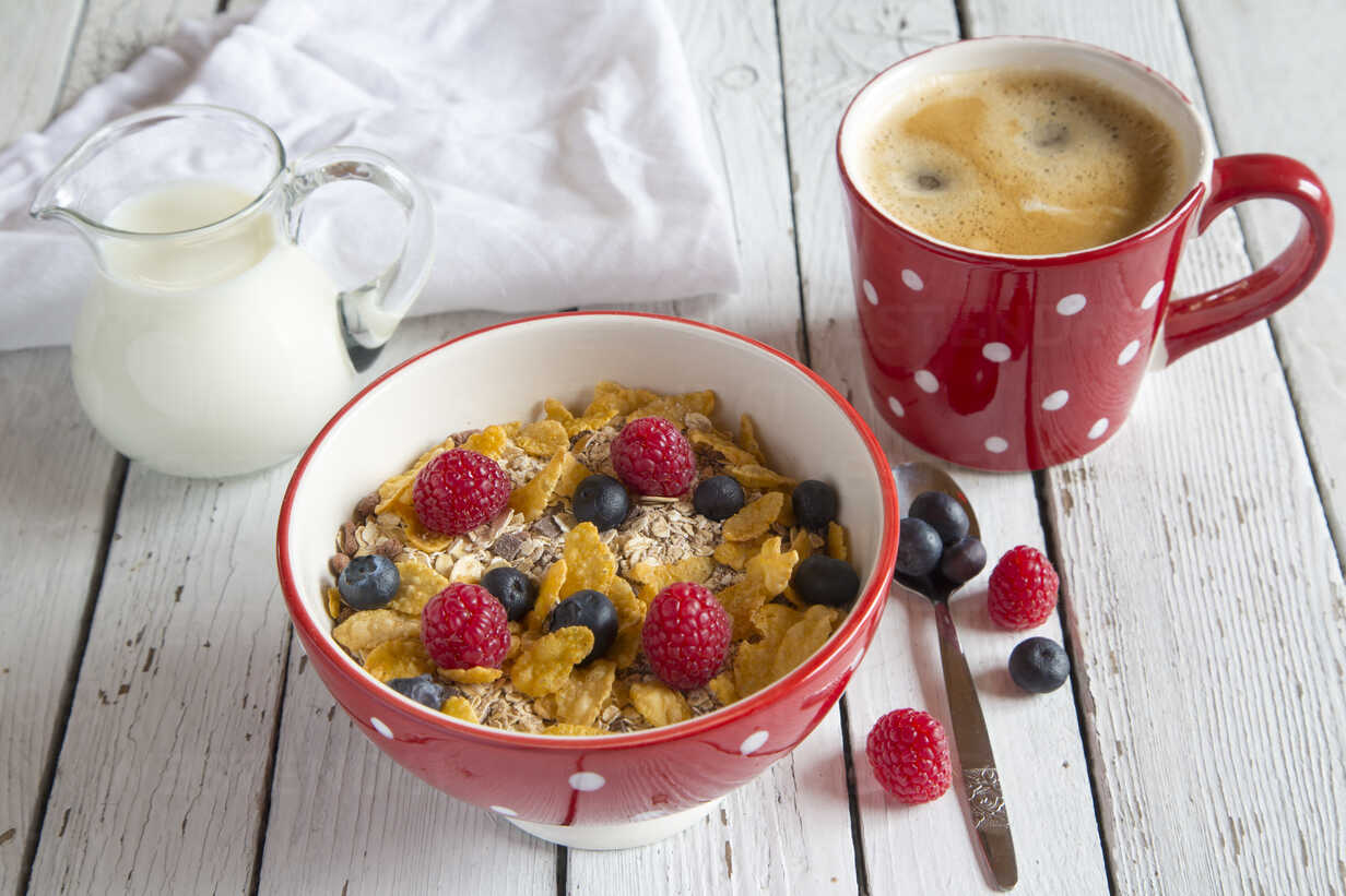 Bowl of granola with fresh fruits, cup of coffee and milk jug on white wood - SARF001078 - Sandra Roesch/Westend61
