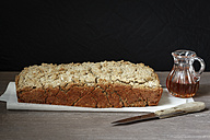 Home-baked buckwheat bread, glass can of honey and kitchen knife on paper and wood - EVGF001018