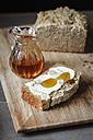 Slice of home-baked buckwheat bread with butter and honey on wooden board - EVGF001027