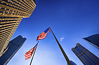 USA, Illinois, Chicago, view to facades of skyscrapers and two American flags from below - SMAF000264