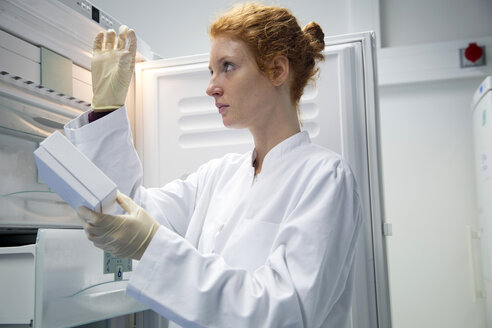 Young female natural scientist controlling a test in biochemistry laboratory - SGF001133