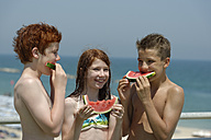 Italy, girl and two teenage boys eating watermelon slices at the beach - LBF000996