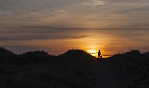 Denmark, Jutland, Lokken, girl in dune at sunset - JBF000209