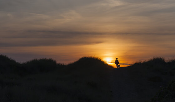Denmark, Jutland, Lokken, girl in dune at sunset - JBF000209