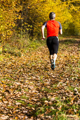 Man running in autumnal forest - STSF000644