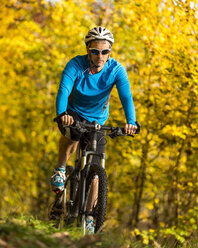Man riding mountaimbike in autumnal forest - STSF000643