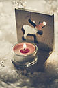 Tea light holder with lightened red candle on artificial snow - SARF001085