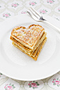 Dish of heart shaped waffles sprinkled with icing sugar on cloth - LVF002372